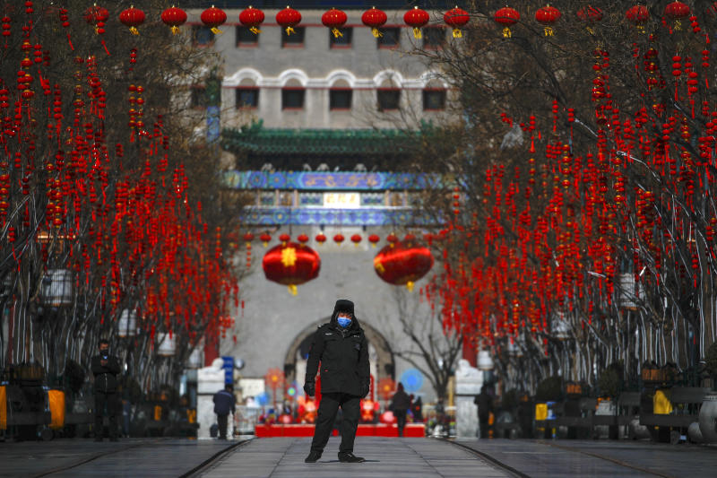 FILE - In this Feb. 16, 2020, file photo, a security guard wearing a face mask walks through a quiet main Qianmen Street, a popular tourist spot in Beijing. As the coronavirus spreads around the world, International health authorities are hoping countries can learn a few lessons from China, namely, that quarantines can be effective and acting fast is crucial. On the other hand, the question before the world is to what extent it can and wants to replicate China's draconian methods. (AP Photo/Andy Wong, File)