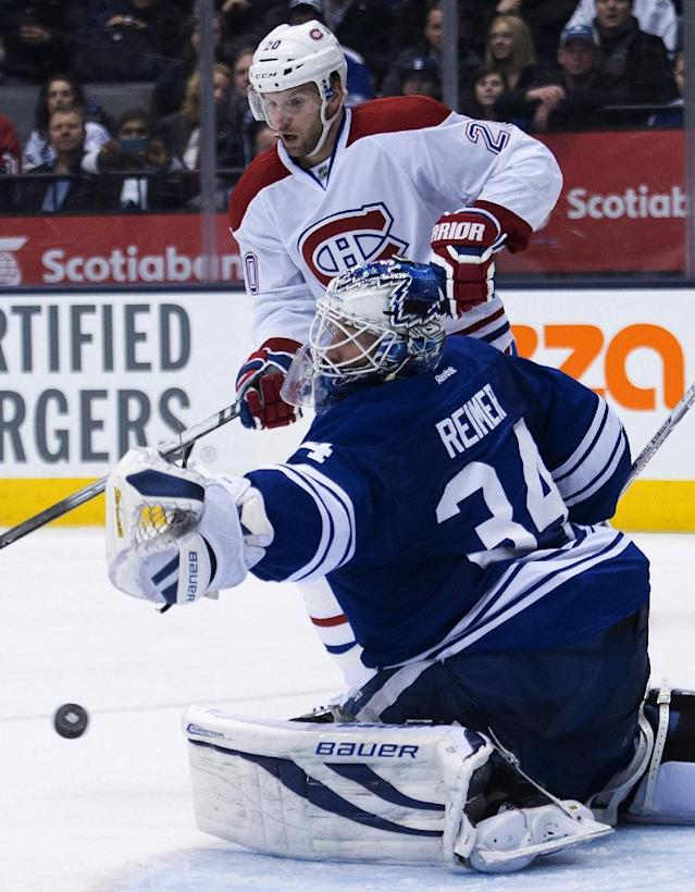 Toronto Maple Leafs' James Reimer, (34) makes a save as Montreal Canadiens forward Thomas Vanek looks on during third period of an NHL hockey game in Toronto on Saturday, March 22, 2014. (AP Photo/The Canadian Press, Nathan Denette)