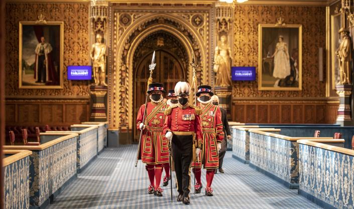 Masked Yeoman warders march along the Royal gallery to take part in the traditional