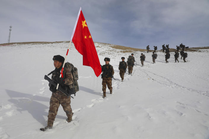 Soldiers march with a Chinese flag during field exercises in the snow near the Kunjerab Pass bordering Pakistan in Taxkorgan in northwest China's Xinjiang Uyhgur Autonomous Region on Jan. 6, 2021. China appointed on Friday, Aug. 6, 2021 a new military commander in restive Xinjiang where authorities have locked up more than a million members of Muslim minorities in what they call a bid to curb terrorism and radicalism. (Chinatopix via AP)