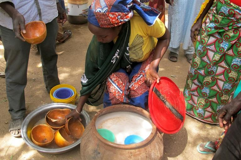 A photo taken on February 23, 2017 shows a woman selling bil-bil, a homemade brew made from millet, sorghum or corn, in Mazogo, in the extreme north of Cameroon