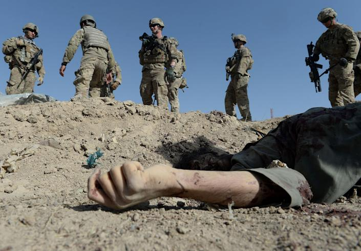 US soldiers over the dead body of an insurgent after a suicide attack in Afghanistan in 2013 (AFP via Getty Images)