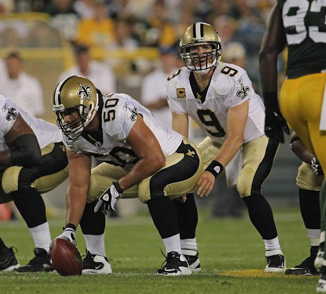 GREEN BAY, WI - SEPTEMBER 08: Olin Kreutz #50 of the New Orleans Saints prepares to snap the ball to Drew Brees #9 against the Green Bay Packers during the NFL opening season game at Lambeau Field on September 8, 2011 in Green Bay, Wisconsin. (Photo by Jonathan Daniel/Getty Images)