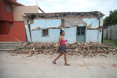 Ximena, 26, an indigenous Zapotec transgender woman also know as Muxe, walks in front of a house destroyed after an earthquake that struck on the southern coast of Mexico late on Thursday, in Juchitan
