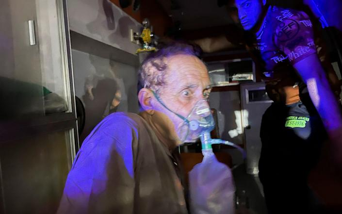 A patient suffering from the coronavirus is prepared for evacuation in an ambulance - Reuters