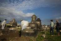 Relatives attend the burial service of 89-year-old Irodina Pinto Ribeiro, who died from COVID-19 related complications, at the Inhauma cemetery in Rio de Janeiro, Brazil, Friday, June 18, 2021. Brazil is approaching an official COVID-19 death toll of 500,000 — second-highest in the world. (AP Photo/Bruna Prado)