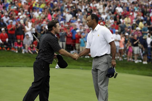 United States team player Tiger Woods, right, shakes hands with International team player Richard Sterne, of South Africa, on the 18th green during the single matches at the Presidents Cup golf tournament at Muirfield Village Golf Club Sunday, Oct. 6, 2013, in Dublin, Ohio. (AP Photo/Darron Cummings)