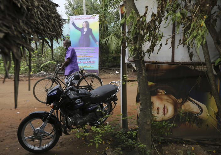An Indian villager walks past a banner featuring U.S. Vice President-elect Kamala Harris with a message wishing her best, in Thulasendrapuram, the hometown of Harris' maternal grandfather, south of Chennai, Tamil Nadu state, India, Wednesday, Jan. 20, 2021. A tiny village in a remote part of South India is gearing up for celebrations ahead of Kamala Harris' inauguration as the first female vice president of the United States. (AP Photo/Aijaz Rahi)