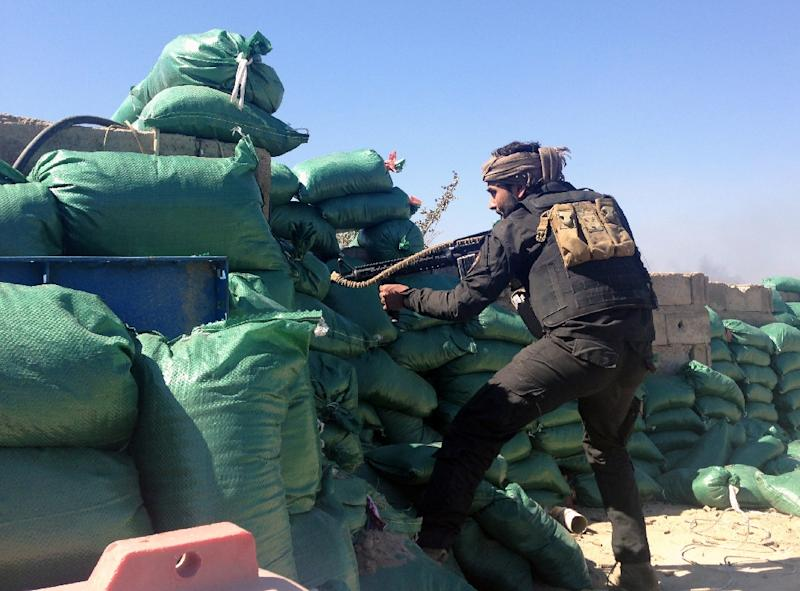 A member of the tribal groups fighting alongside Iraqi security forces takes position behind sandbags during clashes with jihadists in Ramadi on March 11, 2015