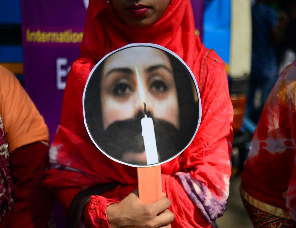 <p>A Bangladeshi woman holding a placard takes part in a rally to mark International Women's Day in Dhaka on March 8, 2018. Thousands of Bangladeshi women, nongovernmental organizations, and rights groups activists took to the streets, demanding safer lives for women in the country as well as an improvement in their social conditions. (Photo: Munir Uz Zaman/AFP/Getty Images) </p>