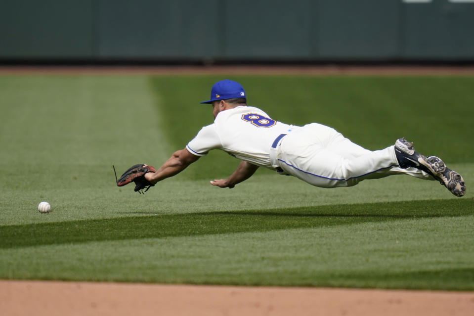 Seattle Mariners second baseman Jack Mayfield dives for but can't get to a grounder for a single by Texas Rangers' Willie Calhoun in the sixth inning of a baseball game Sunday, May 30, 2021, in Seattle. (AP Photo/Elaine Thompson)