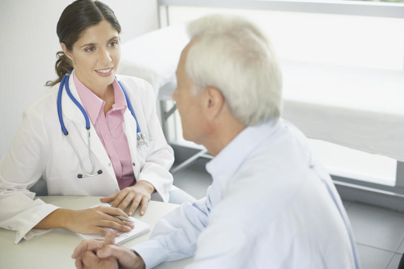 A female doctor sitting at a table talking to a male patient