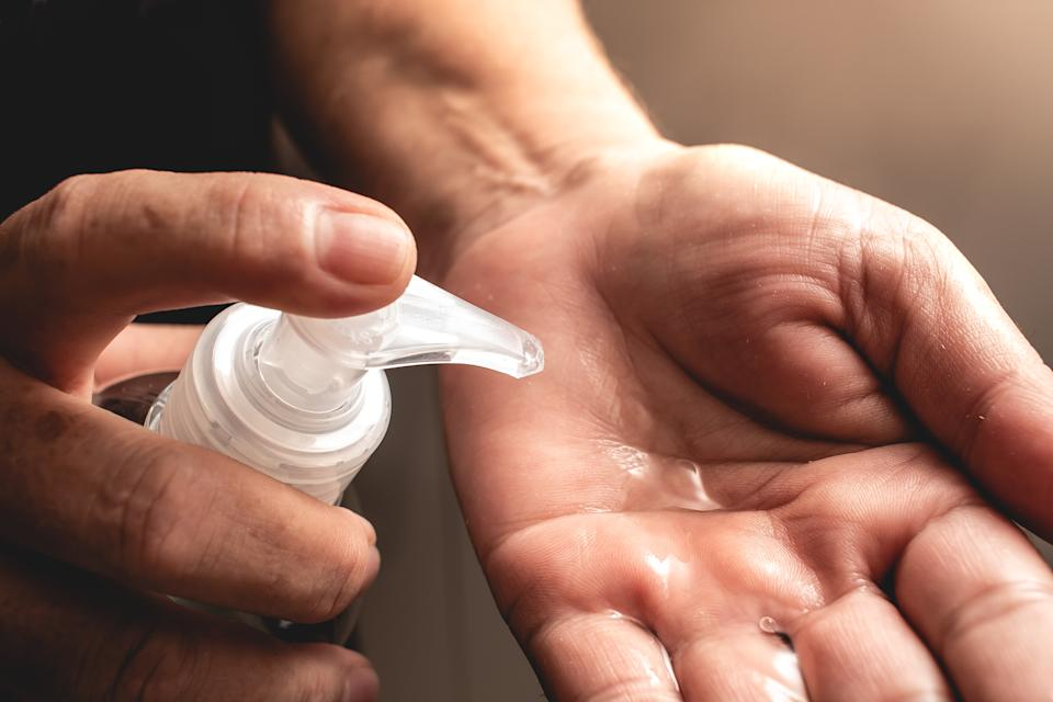 A woman holding a Hand sanitizer ( Álcool gel).