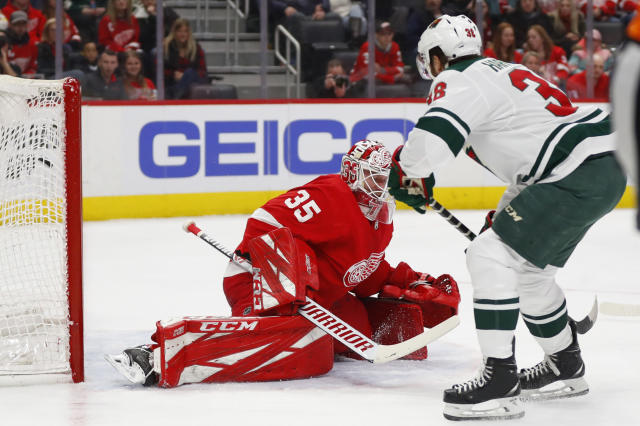 Minnesota Wild right wing Ryan Hartman (38) scores on Detroit Red Wings goaltender Jimmy Howard (35) in the first period of an NHL hockey game Thursday, Feb. 27, 2020, in Detroit. (AP Photo/Paul Sancya)