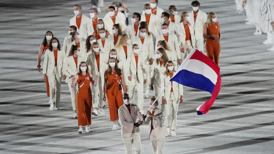 <p>Keet Oldenbeuving and Churandy Martina, of the Netherlands, carry their country's flag during the opening ceremony in the Olympic Stadium at the 2020 Summer Olympics, Friday, July 23, 2021, in Tokyo, Japan. (AP Photo/David J. Phillip)</p>