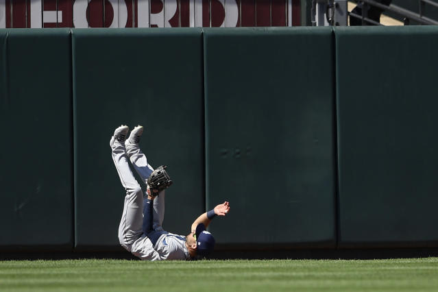 Tampa Bay Rays center fielder Kevin Kiermaier tumbles on the ground after he made an attempt on a ball that went for a two-run home run by Baltimore Orioles' Stevie Wilkerson during the seventh inning of the first baseball game of a split doubleheader, Saturday, July 13, 2019, in Baltimore. The Orioles won 2-1. (AP Photo/Nick Wass)