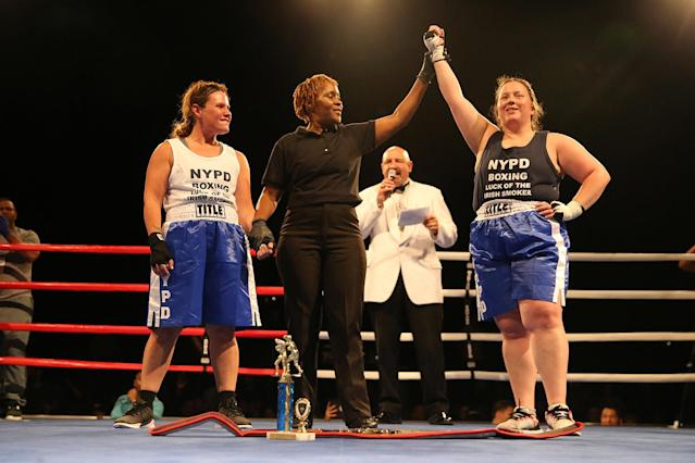 <p>Katie Walsh's arm is raised in the air by referee as the winner of the Female Grudge Match over Stacy Weinstein at the NYPD Boxing Championships at The Theater at Madison Square Garden on June 8, 2017. (Photo: Gordon Donovan/Yahoo News) </p>