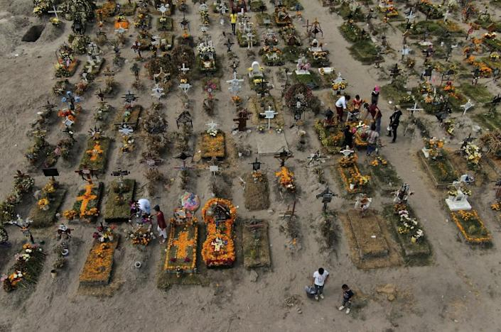 People visit the graves of their relatives buried at the Valle de Chalco municipal cemetery, some decorated ahead of the Day of the Dead holiday, on the outskirts of Mexico City, Thursday, Oct. 29, 2020. Mexico's Day of the Dead celebration this weekend won't be the same in a year so marked by death, in a country where more than 90,000 people have died of COVID-19. (AP Photo/Fernando Llano)