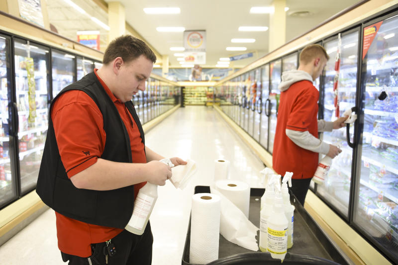 West Lawn, PA - March 23: Weis Markets employees (L-R) Joe Dietrich and Nate Hable clean freezer door handles shortly before closing Monday night March 23, 2020 at the Weis Market in West Lawn. Grocery stores are an industry that is hiring during the coronavirus outbreak, due to increased demands on the stores.(Photo by Lauren A. Little/MediaNews Group/Reading Eagle via Getty Images)