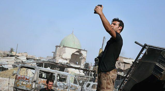 An Iraqi soldier takes a selfie in Mosul after the city was recaptured from IS on July 10. Source: AAP
