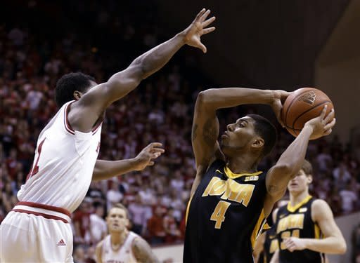 Indiana guard Kevin Ferrell, left, defends Iowa forward Roy Devyn Marble in the first half of an NCAA college basketball game in Bloomington, Ind., Saturday, March 2, 2013. (AP Photo/Michael Conroy)