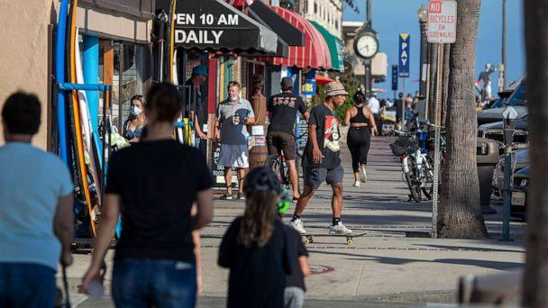 PHOTO: People walk and skateboard on the sidewalk past businesses on July 20, 2020, in Newport Beach, Calif. (Allen J Schaben/Los Angeles Times via Shutterstock)
