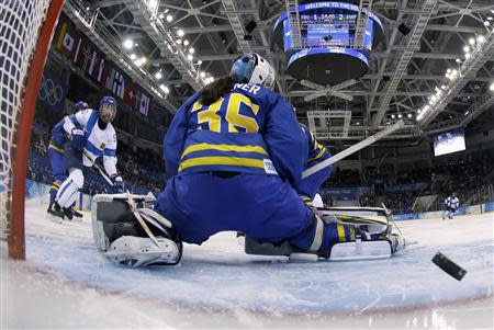 Finland's Nuutinen shoots past Sweden's goalie Wallner to score during the third period of their women's ice hockey playoffs quarter-final game at the Sochi 2014 Winter Olympic Games