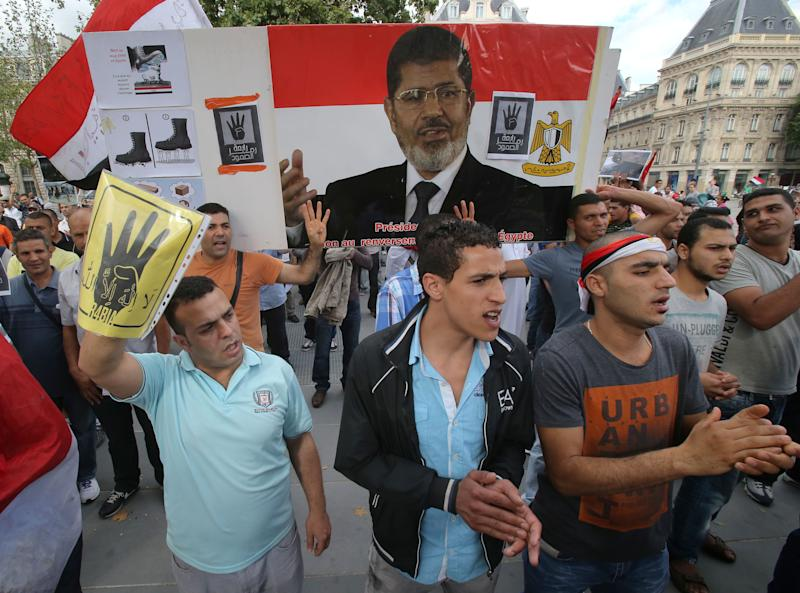 Egyptian supporters of ousted Egyptian President Mohammed Morsi living in France, protest in Paris, Sunday, Aug. 18, 2013. A picture of ousted Egyptian President is seen.(AP Photo/Michel Euler)