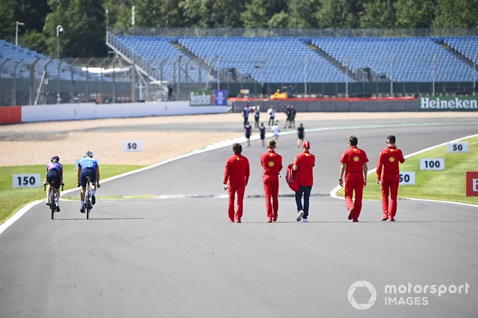 """Valtteri Bottas, Mercedes-AMG Petronas F1 and Tiffany Cromwell cycle the track past Sebastian Vettel, Ferrari as he walks the track with his engineers <span class=""""copyright"""">Mark Sutton / Motorsport Images</span>"""