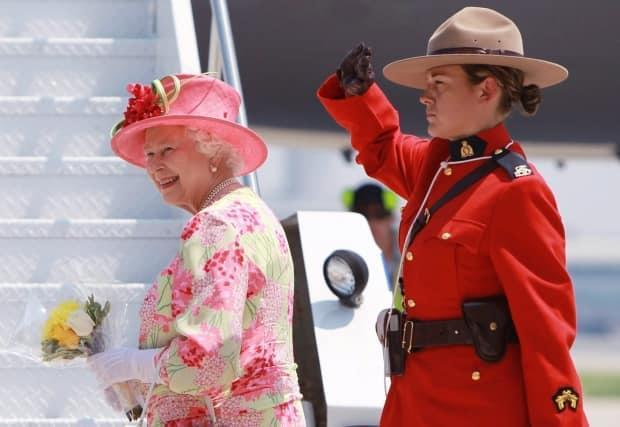 Queen Elizabeth is saluted by a Royal Canadian Mounted Police officer before boarding her plane at Pearson International Airport in Toronto Tuesday, July 6, 2010. (Darren Calabrese/The Canadian Press - image credit)