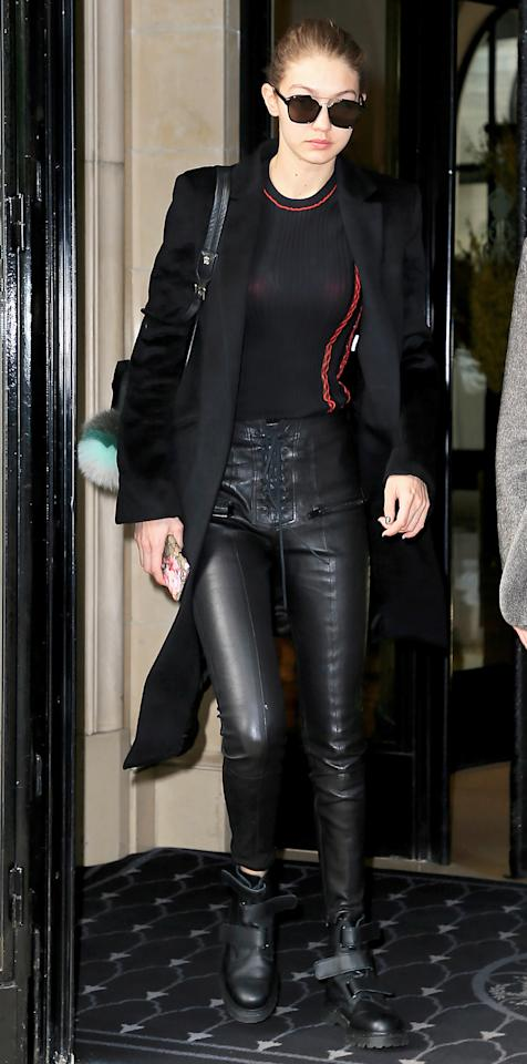 """<p>Hadid took to the streets of Paris in sleek lace-up leather pants (shop a similar look <a rel=""""nofollow"""" href=""""http://www.anrdoezrs.net/links/7799179/type/dlg/sid/ISGigiSSLeatherPantsIJApril/http://www.fwrd.com/product-rag-bonejean-lace-up-leather-pants-in-washed-black/RANX-WP6/?d=F&utm_source=polyvore&utm_medium=affiliate&utm_content=Pants&source=polyvore&device=desktop&utm_campaign=dom_p_us"""">here</a>), her go-to velcro Doc Martens ($140; <a rel=""""nofollow"""" href=""""https://click.linksynergy.com/fs-bin/click?id=93xLBvPhAeE&subid=0&offerid=401480.1&type=10&tmpid=14379&RD_PARM1=http%3A%2F%2Fwww.shoebuy.com%2Fdr-martens-coralia-adjustable-strap-boot%2F803331%2F1734270%3F&u1=ISGigiSSDocMartenIJApril"""">shoebuy.com</a>), a long black coat, and a semi-sheer black sweater with red stitching. Lookin' fierce, girl!</p>"""