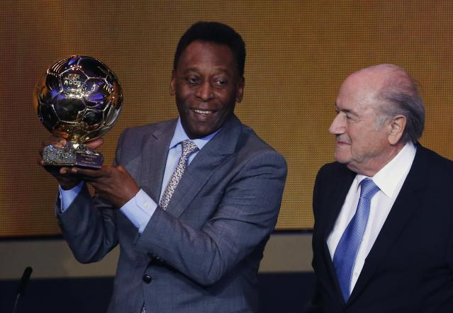 Pele holds up his FIFA honorary award beside FIFA President Sepp Blatter during the FIFA Ballon d'Or 2013 soccer awards ceremony in Zurich