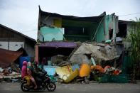 Locals ride a motorbike past a collapsed house following an earthquake in Mamuju