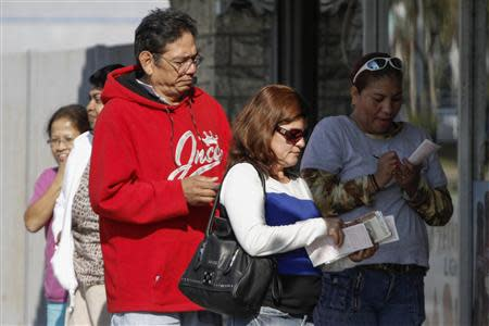 People wait in line to purchase Mega Millions lottery tickets at Bluebird Liquor in Hawthorne, California December 13, 2013. REUTERS/Jonathan Alcorn