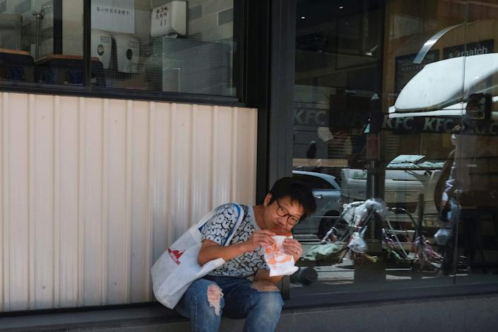 """A woman has lunch outside a restaurant at a mall after the government banned dine-in services in Hong Kong on July 30, 2020. <p class=""""copyright"""">REUTERS/Tyrone Siu</p>"""