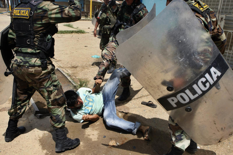 A miner is roughed up by riot police officers during clashes in Puerto Maldonado, Peru, Wednesday, March 14, 2012. Thousands of illegal gold miners battled police for control of a regional capital in the Amazon basin on Wednesday and at least three people were killed by gunfire. The miners are fighting government efforts to regulate small-scale gold extraction, which is ravaging the rain forest, contaminating it with tons of mercury. (AP Photo/ Miguel Vizcarra)
