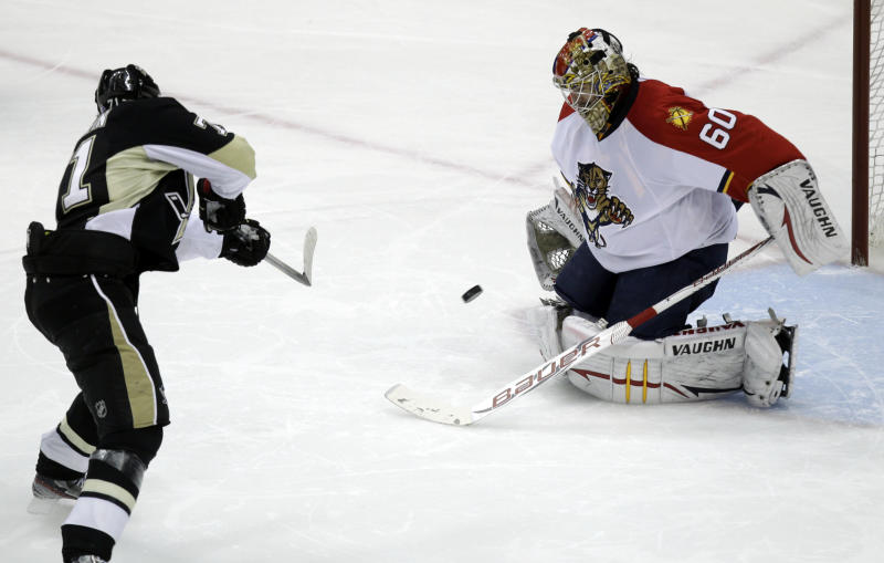 Pittsburgh Penguins' Evgeni Malkin, left, scores on Florida Panthers goalie Jose Theodore (60) during a shootout in an NHL hockey game in Pittsburgh Friday, March 9, 2012. The Penguins won 2-1. (AP Photo/Gene J. Puskar)