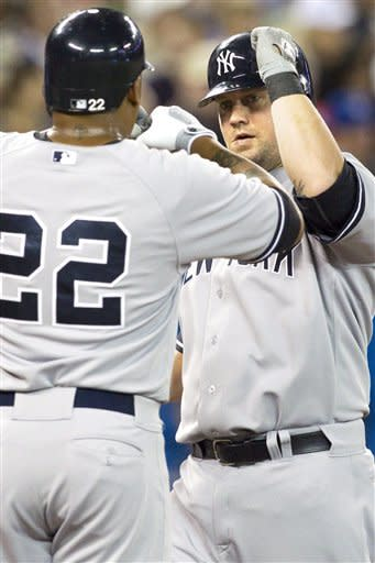 New York Yankees' Casey McGehee, right, celebrates with Andruw Jones after hitting a three run homer off Toronto Blue Jays pitcher Aaron Laffey during the fourth inning of a baseball game in Toronto on Saturday, Aug. 11 , 2012. (AP Photo/The Canadian Press, Chris Young)