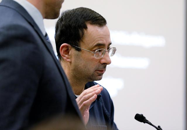 FILE PHOTO: Dr. Larry Nassar, a former team USA Gymnastics doctor who pleaded guilty in November 2017 to sexual assault charges, raises his hand to be sworn in for his sentencing hearing in Lansing, Michigan, U.S., January 16, 2018. REUTERS/Brendan McDermid/File Photo