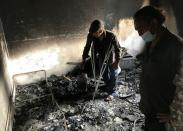 Lyazid Tazibt stands with his brother Khelaf inside their home that was burnt following a wildfire in the village of Ait Sid Ali