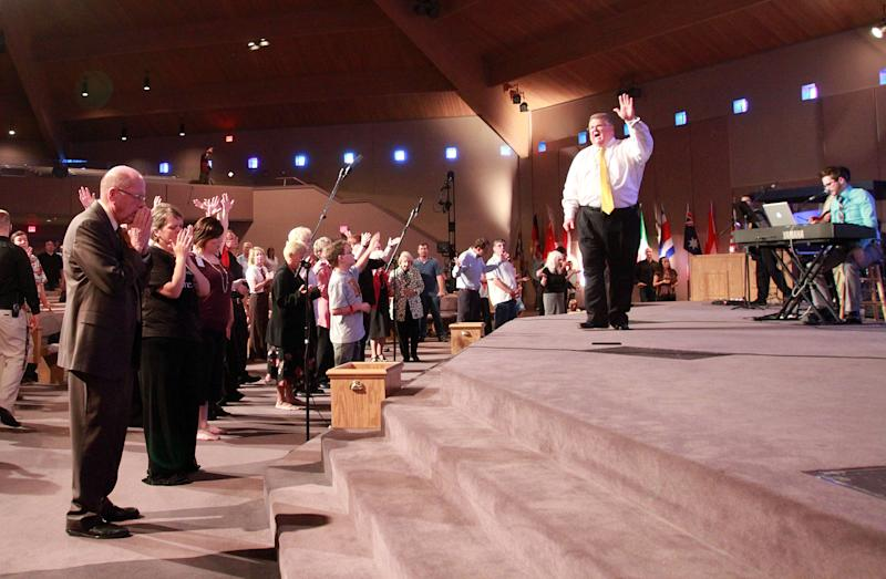In this March 25, 2012, photo, Brownsville Assembly senior pastor Rev. Evon Horton preaches to his congregation in Pensacola, Fla. The church that was home to the largest Pentecostal outpouring in U.S. history is on the edge of financial ruin. The revival that drew some 5,500 people nightly at its height saddled the congregation with an $11.5 million debt that members were left to pay off after both the out-of-town throngs and former Rev. John Kilpatrick moved on. The red ink is mostly unknown outside the congregation. (AP Photo/John David Mercer)