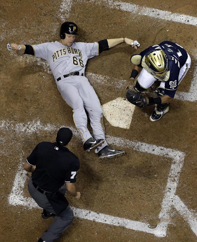Milwaukee Brewers catcher Martin Maldonado, right, tags out Pittsburgh Pirates' Justin Morneau (66) at home during the fifth inning of a baseball game on Wednesday, Sept. 4, 2013, in Milwaukee. Morneau tried to score from first on a hit by Marlon Byrd. (AP Photo/Morry Gash)