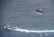 Ecuadorian Navy vessels surround a fishing boat after detecting a fishing fleet of mostly Chinese-flagged ships in the Pacific Ocean