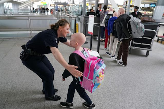 <p>Baraka Lusambo, 7, a Tanzanian with albinism who had his arm chopped off in a witchcraft-driven attack, hugs Teresa Piasecka, supervisory officer for U.S. Customs and Border Protection, before his flight home to Tanzania, at JFK airport in New York, June 6, 2017. (Photo: Carlo Allegri/Reuters) </p>