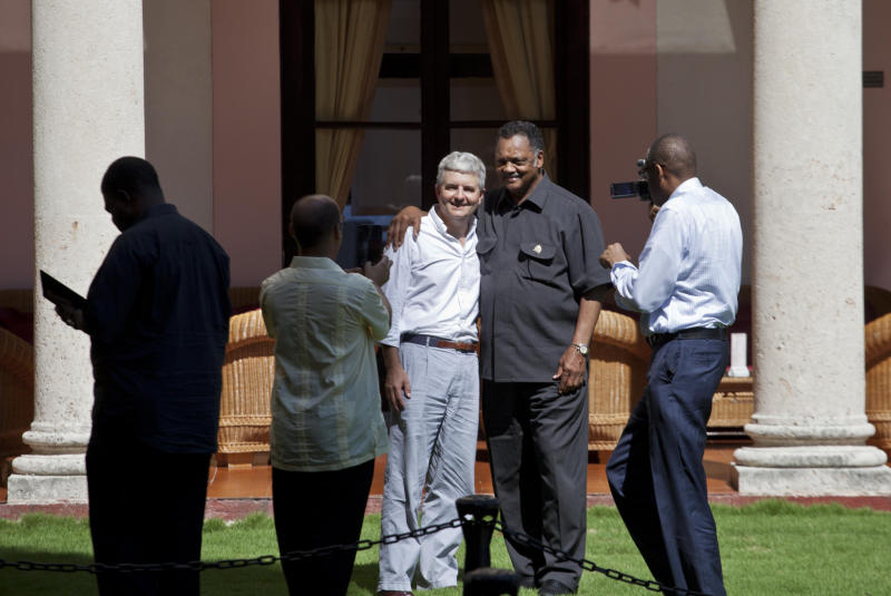 Rev. Jesse Jackson, center right, poses for a photo with Conrad Tribble, the No. 2 official at the U.S. Interests Section in Havana, on the lawn of the Hotel Nacional in Havana, Cuba, Saturday, Sept. 28, 2013. Jackson says he is in town for talks with religious leaders about their concerns for the poor, and peaceful relations between Cuba, the United States and the rest of the Caribbean. Jackson says he also hopes to meet with jailed American government subcontractor Alan Gross. (AP Photo/Ramon Espinosa)