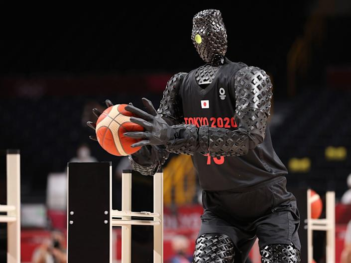 A robot takes shots on the basketball court during halftime of USA-France at Tokyo 2020.