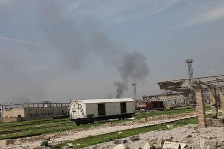 Smoke rises up from buildings as train cars are seen in the railway station in Mosul, Iraq