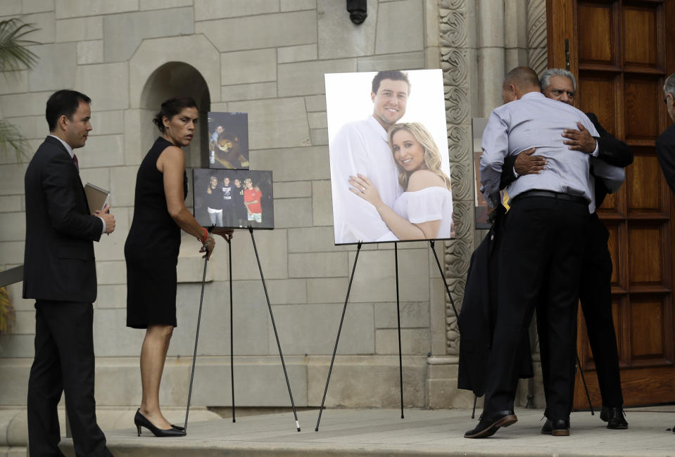 Debbie Hetman, left, mother of Los Angeles Angels pitcher Tyler Skaggs, stands in front of images of Skaggs during a memorial in his honor at the St. Monica Catholic Church Monday, July 22, 2019, in Los Angeles. (AP Photo/Marcio Jose Sanchez)