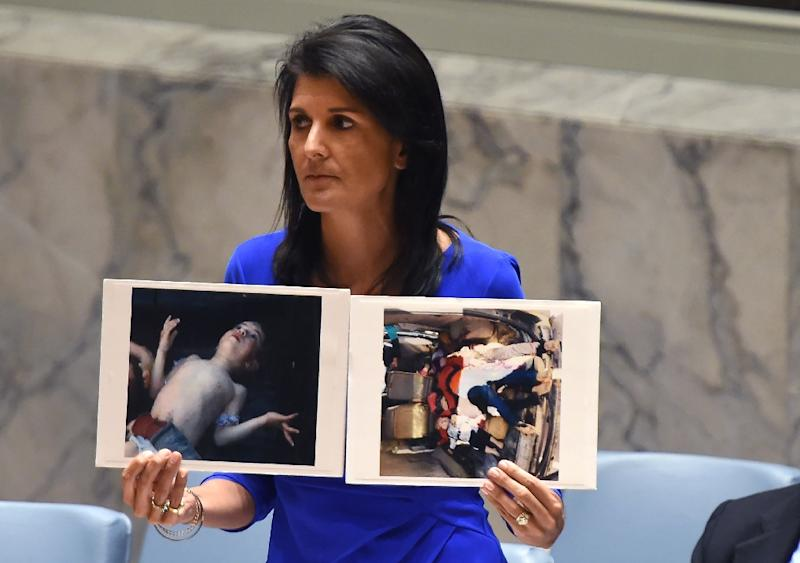US Ambassador to the UN Nikki Haley holds photos of victims as she speaks as the UN Security Council meets in an emergency session on April 5, 2017, about the suspected chemical attack that killed civilians, including many children, in Syria