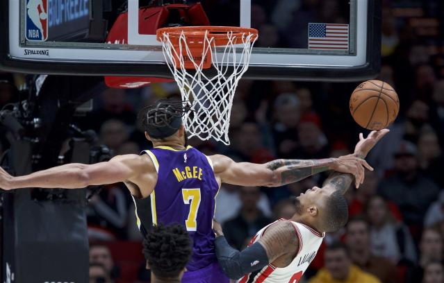 Portland Trail Blazers guard Damian Lillard, right, is fouled by Los Angeles Lakers center JaVale McGee during the first half of an NBA basketball game in Portland, Ore., Saturday, Dec. 28, 2019. (AP Photo/Craig Mitchelldyer)